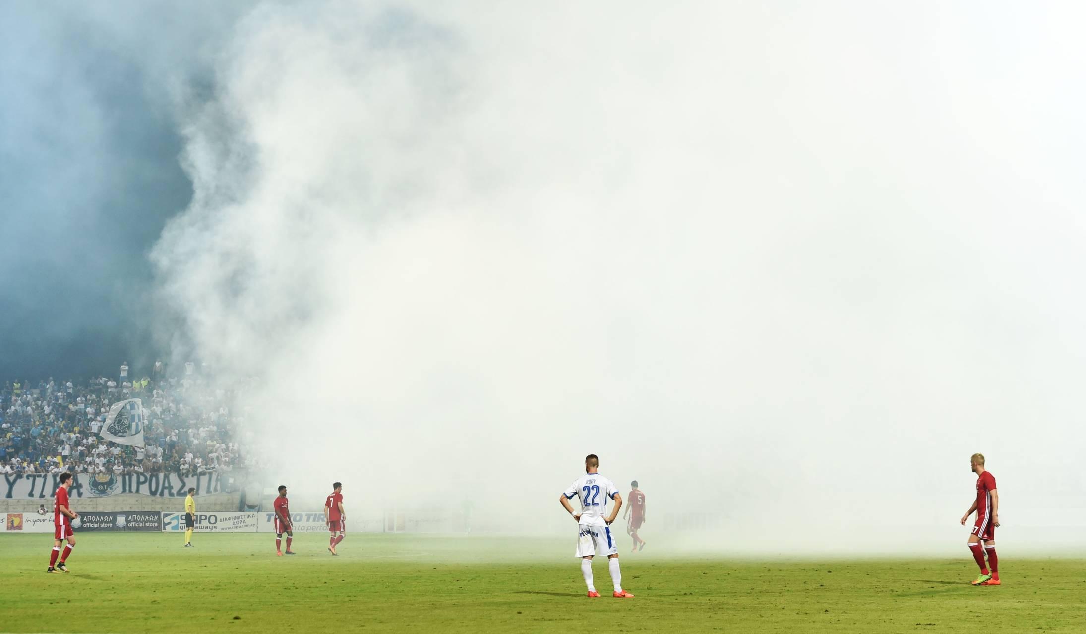 The Apollon Limassol fans throw flares onto the pitch.