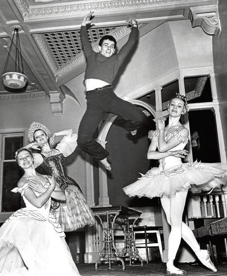 1977: A break during HMT rehearsals, but ballet star Graham Bart is still flying high, watched by Veronica Butcher, Wendy Roe and Patricia Merrin.