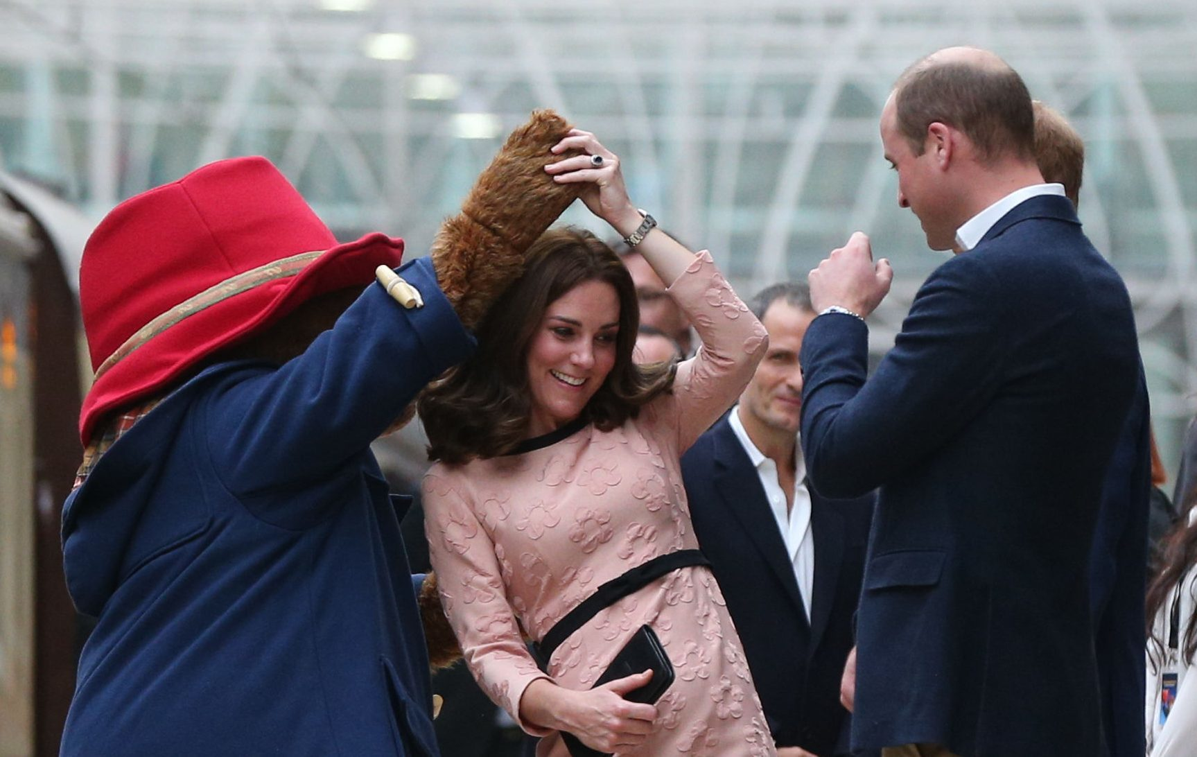 The Duke of Cambridge watches as his wife the Duchess of Cambridge dances with a costumed figure of Paddington bear