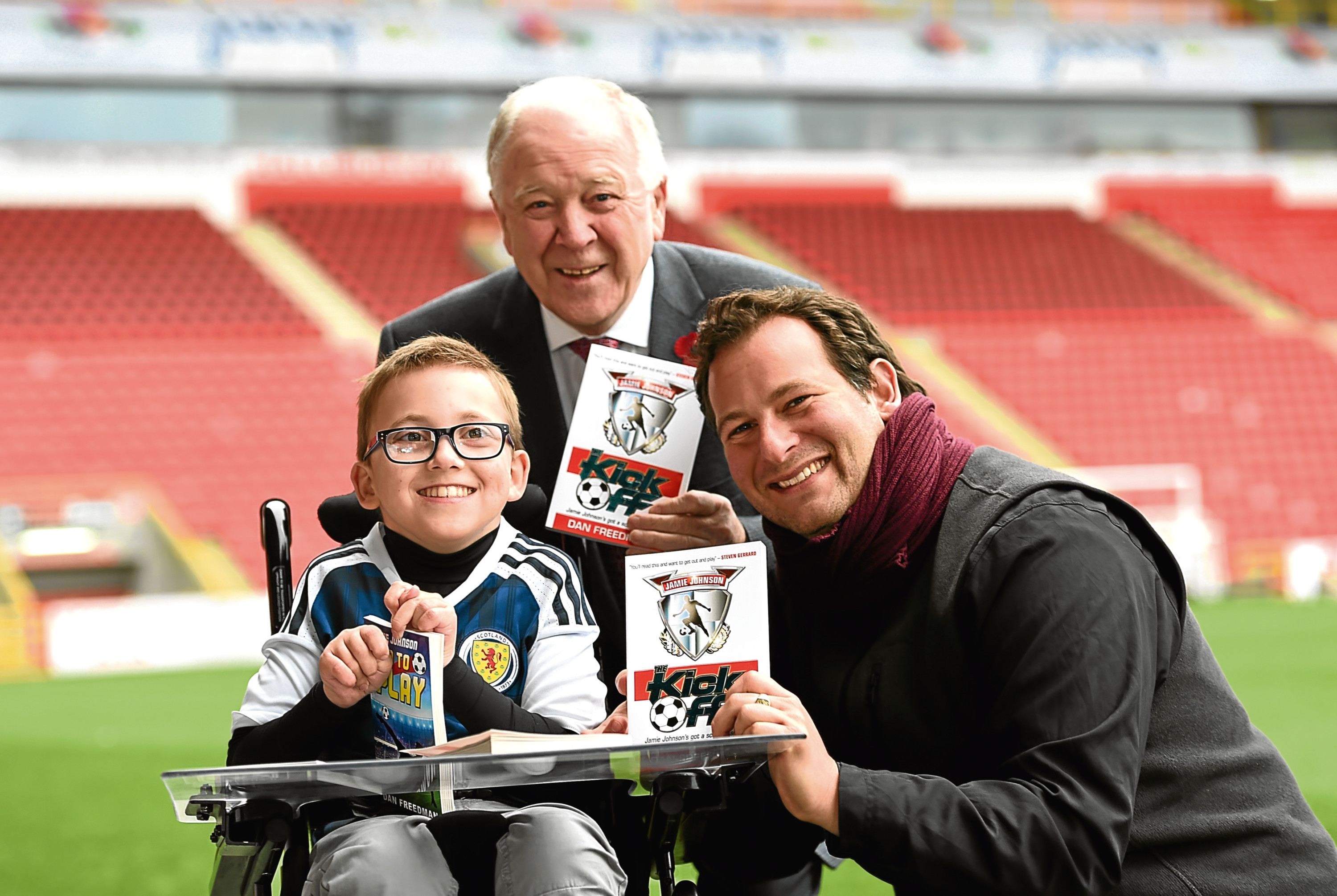 Former Scotland manager Craig Brown, Finlay Sangster, 12 and author Dan Freedman at Pittodrie Stadium, Aberdeen