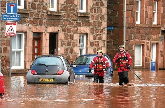 Fireman walk through floodwater on the high street in Stonehaven after heavy flooding.