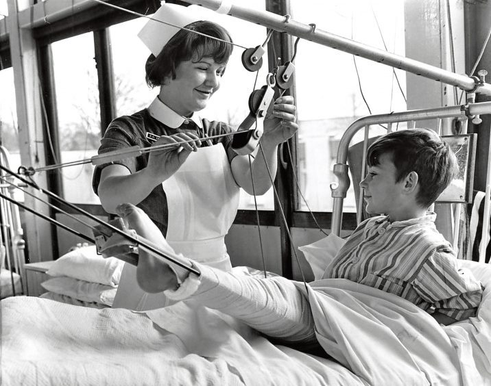 1968: A nurse smiles while she helps a boy with his leg in splints.