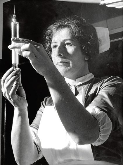 1964: Staff nurse Sister Margaret Thomson with an injection.