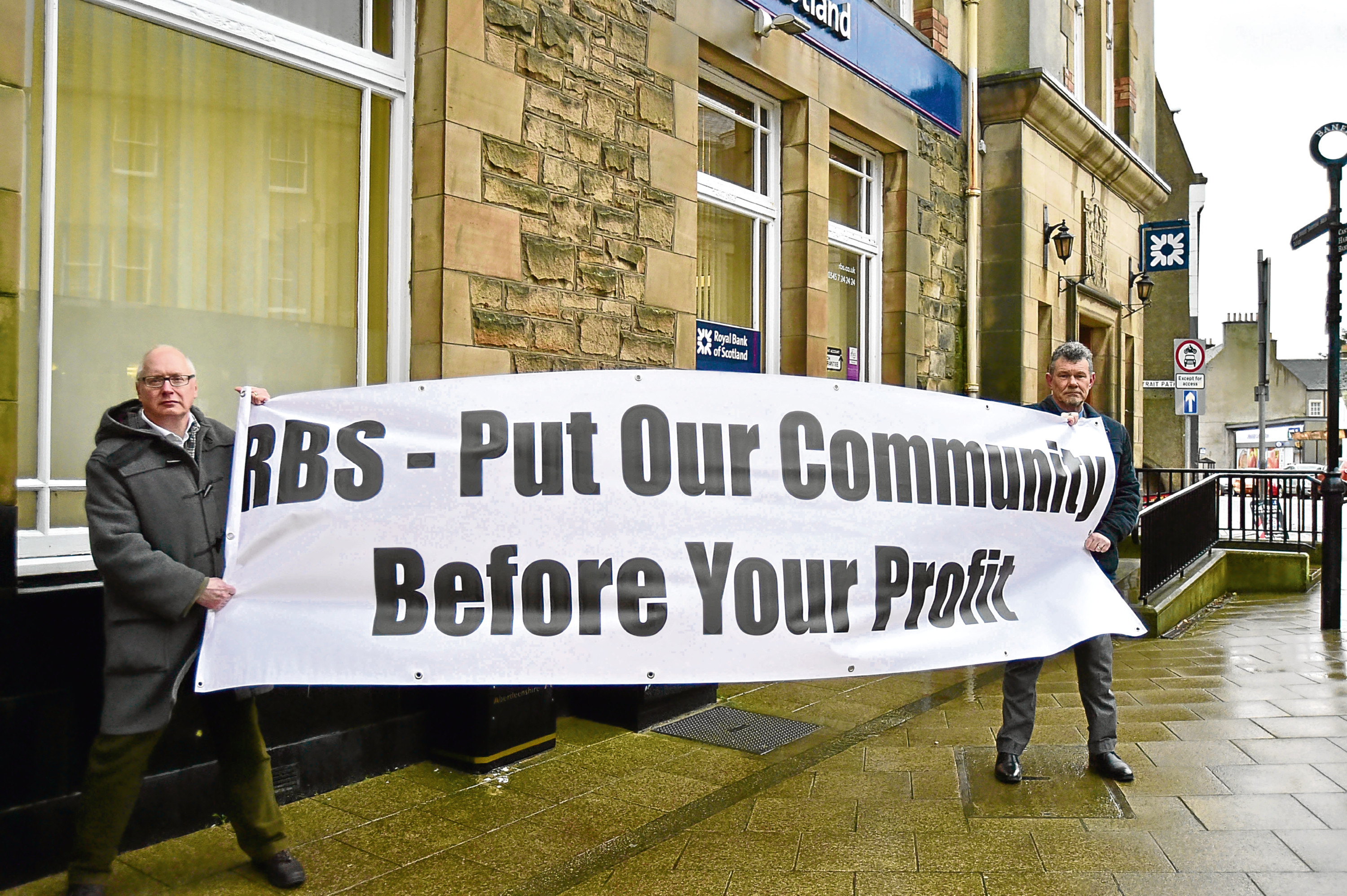 Cllrs Glen Reynolds and Ross Cassie demonstrate outside the RBS in Banff