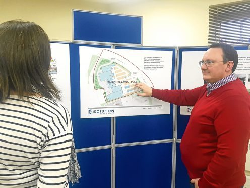 Alex Mitchell of Zander Planning explains the layout to an exhibition visitor.
