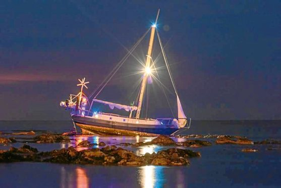 Yacht stranded on rocks in Stonehaven.