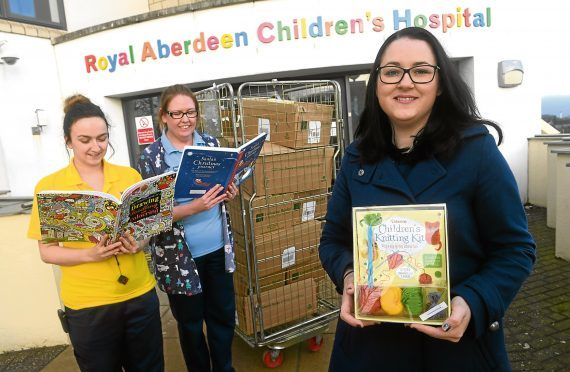 Tegan Kemp, right,  raised money to give every child in Royal Aberdeen Children's Hospital a book for Christmas. Tegan is pictured with play leader Megan Davidson, left, and Wendy Joss, play specialist.