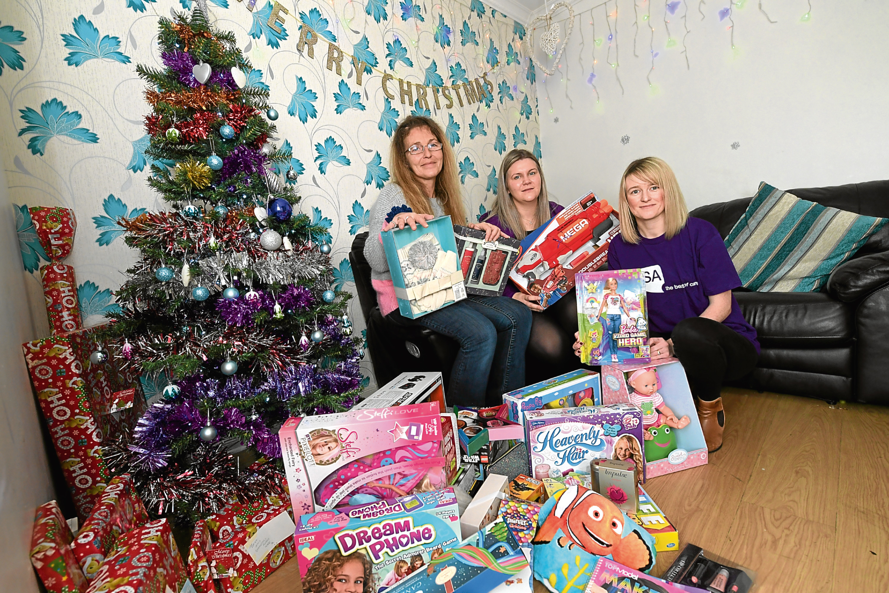 Jeanie McAllister had £2,500 of Christmas presents stolen from her garden shed and VSA have given her replacement presents. Jeanie with, from left, Vicki Youngson and Jennifer Mitchell from VSA.