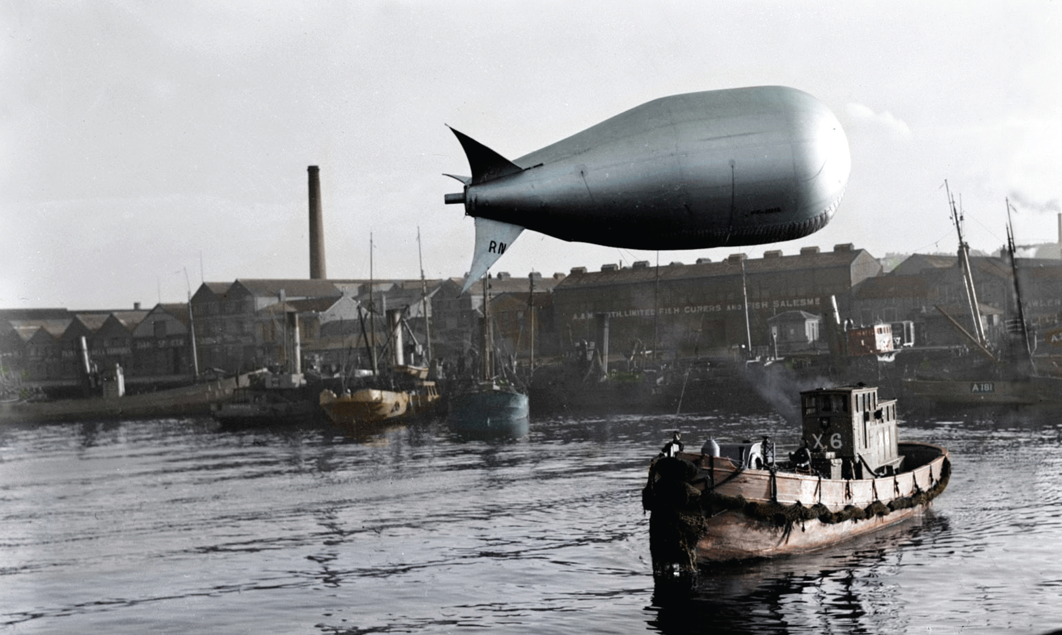 A Royal Naval airship trails along after a fishing boat in this industrial view of the Harbour as a deckhand watches on in this amazing photo.