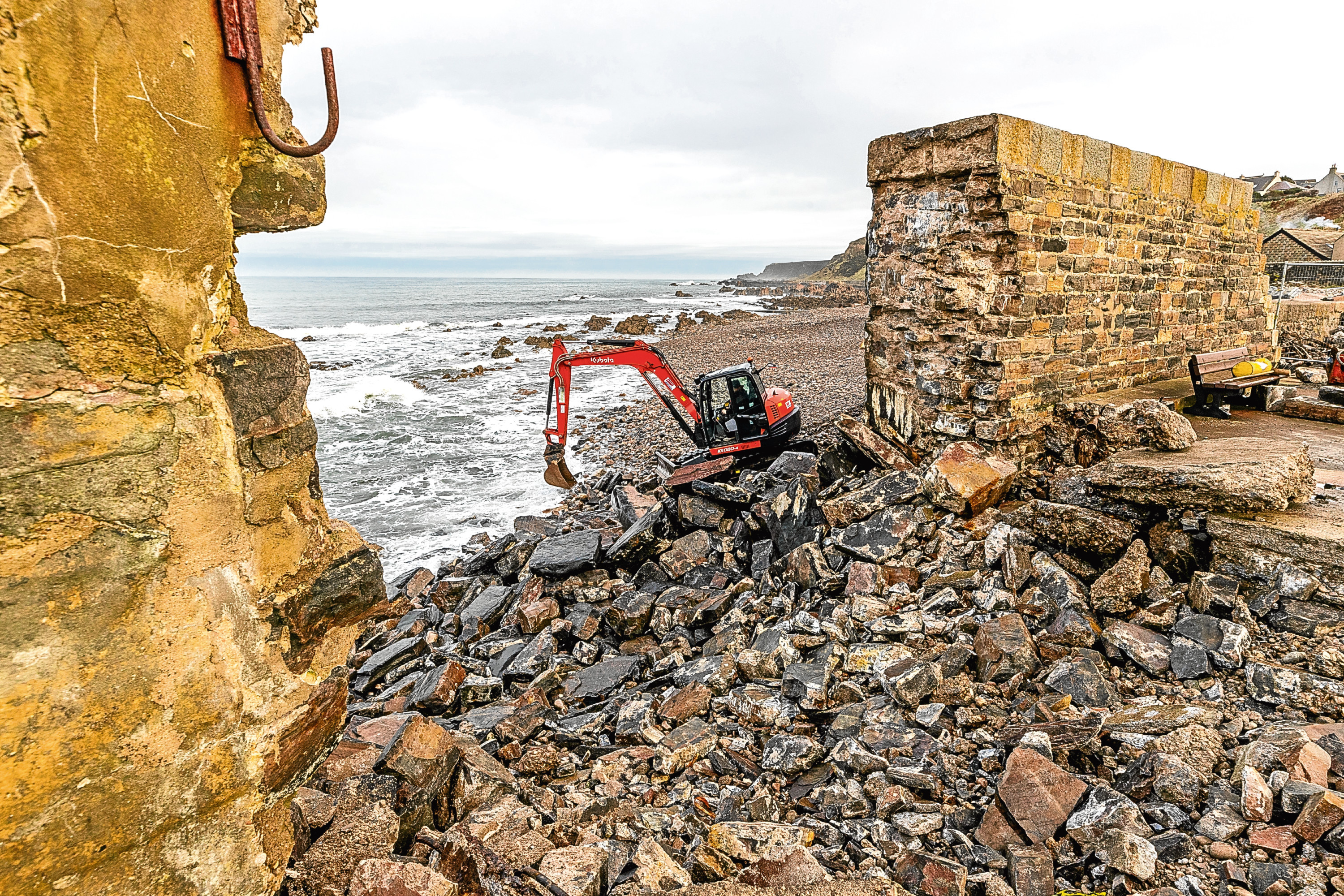This is Lochshell Engineering at work to the exterior side of the damaged pier at Cullen Harbour, Moray. Thuis is them retrieving the stones from the sea in order that the wall can be rebuilt.