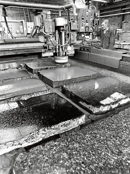 1975: Bob Taylor polishes seven granite slabs at once with an automatic polisher at Robertson Granite Yard.