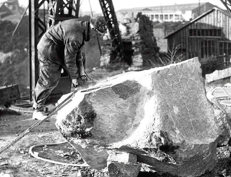 1948: D Donaldson works on a big block of granite. Note the ladder used for getting on to the top.
