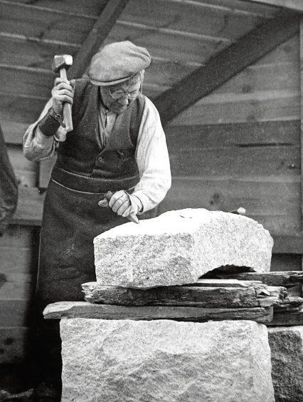 1930s: A worker in the 1930s shapes a granite block with a hammer and chisel