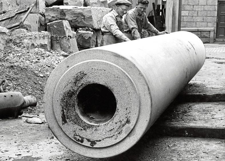 1954: Workmen examine a granite roller at a yard in Aberdeen.