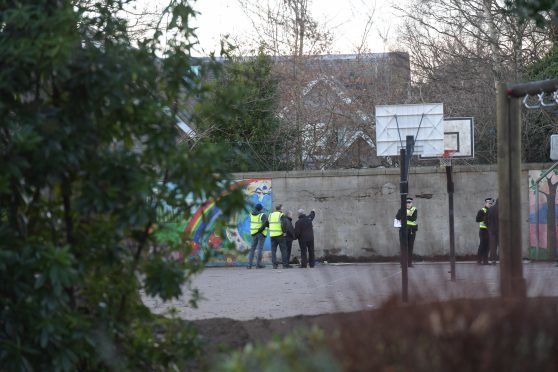 Officials and police view the wall