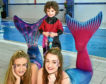 Four-year-old Summer Russell meets mermaids Luna, left, and Serena.