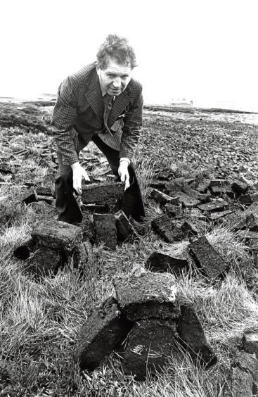 1977: Scott Smith shows off some peat cuttings at New Pitsligo.