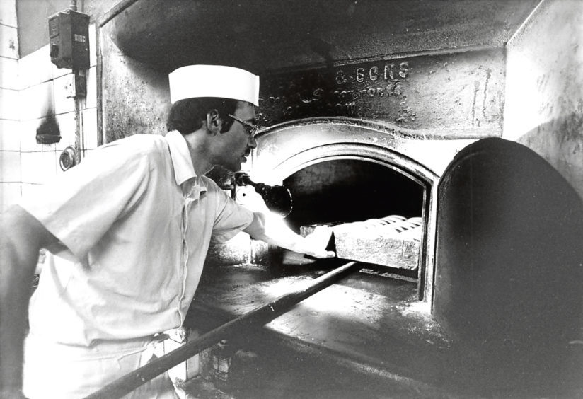1984: Adam Duguid at Chalmers' Bakery, Bucksburn, puts a batch of bread in the oven.