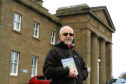 "Courier News - Janet Thomson story - Montrose Royal Infirmary. Picture shows; local  historian and author, Forbes Inglis outside Montrose Royal Infirmary today, where a bust of Susan Carnegie has been removed, with a copy of his book ""The Sea Enriches"". Wednesday 7th March 2018."