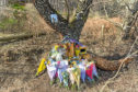 Floral tributes and photos left at the crash scene on the B9015 Rothes to Mosstodloch road.