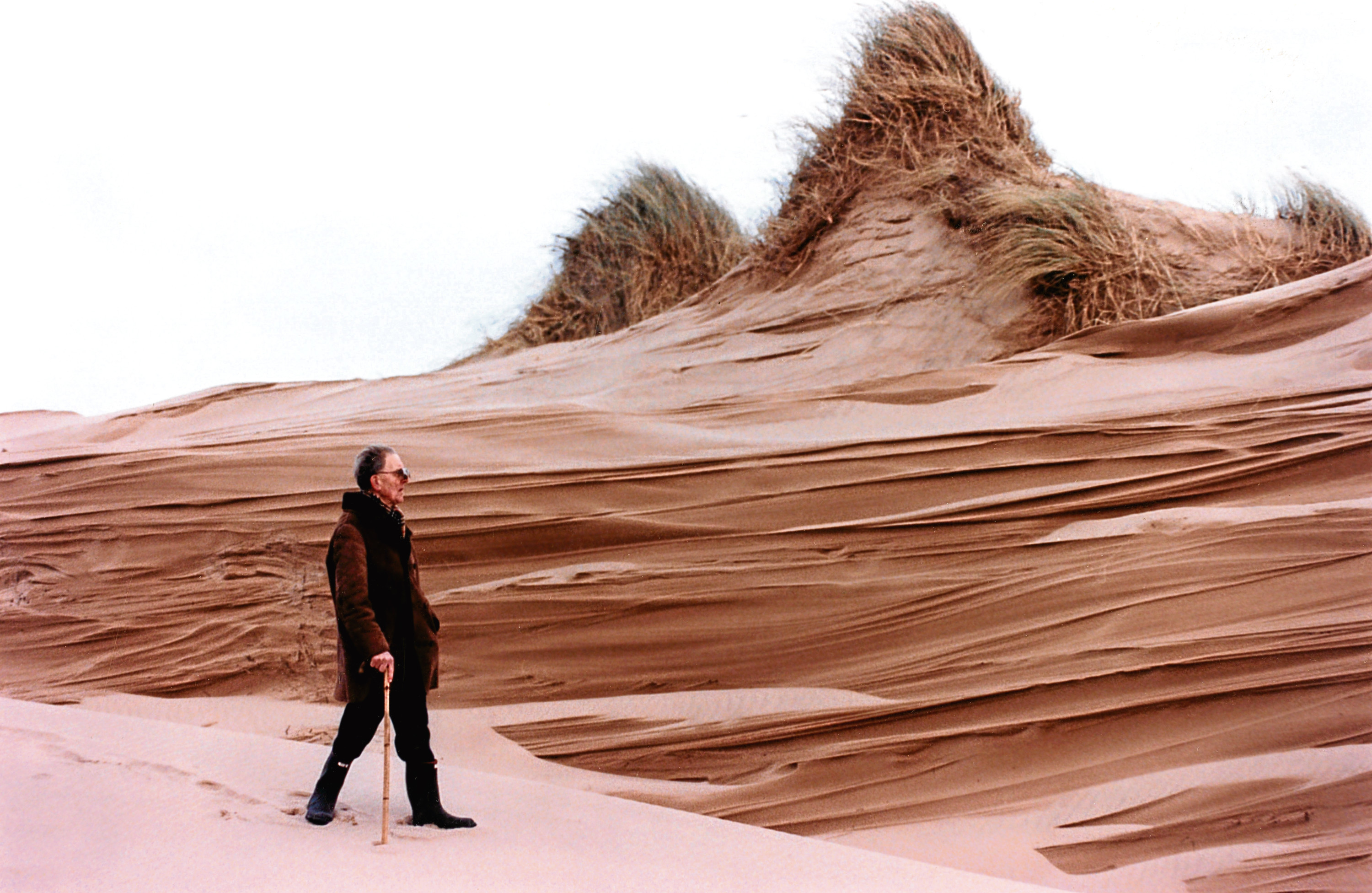 1997: Paul Miller takes a walk past dunes that have been eroded by the wind.