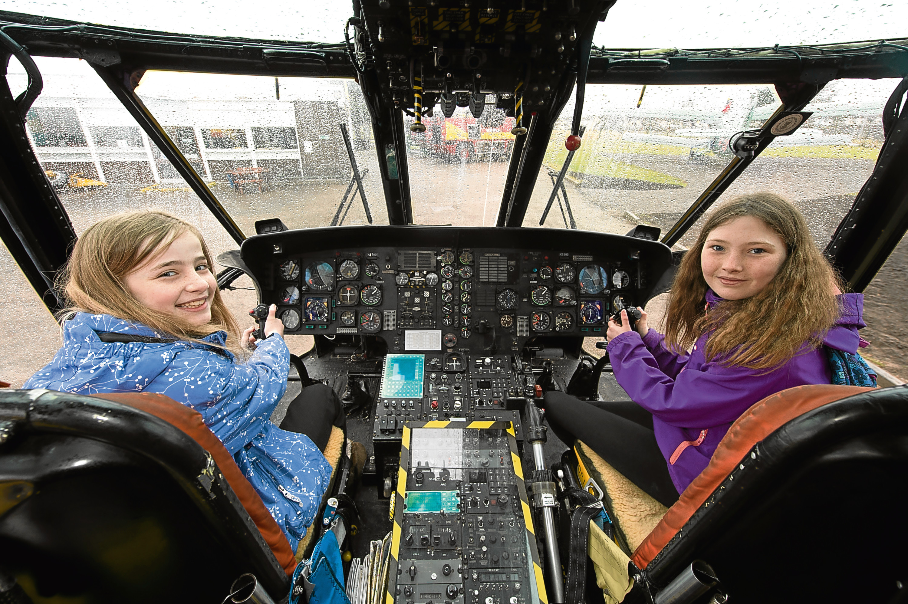 Mia Jackson, left, and Drew Whitmore are pictured in the cockpit of a sea king.