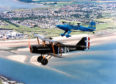 1993: Two bi-planes taking part in the Scottish Wings and Wheels Extravaganza soar with the Grampians in the distance. Aberdeen-born surgeon, Neil Geddes, Bridge of Weir, flew the 7/8-scale replica of an SE5A (bottom), which he built himself.