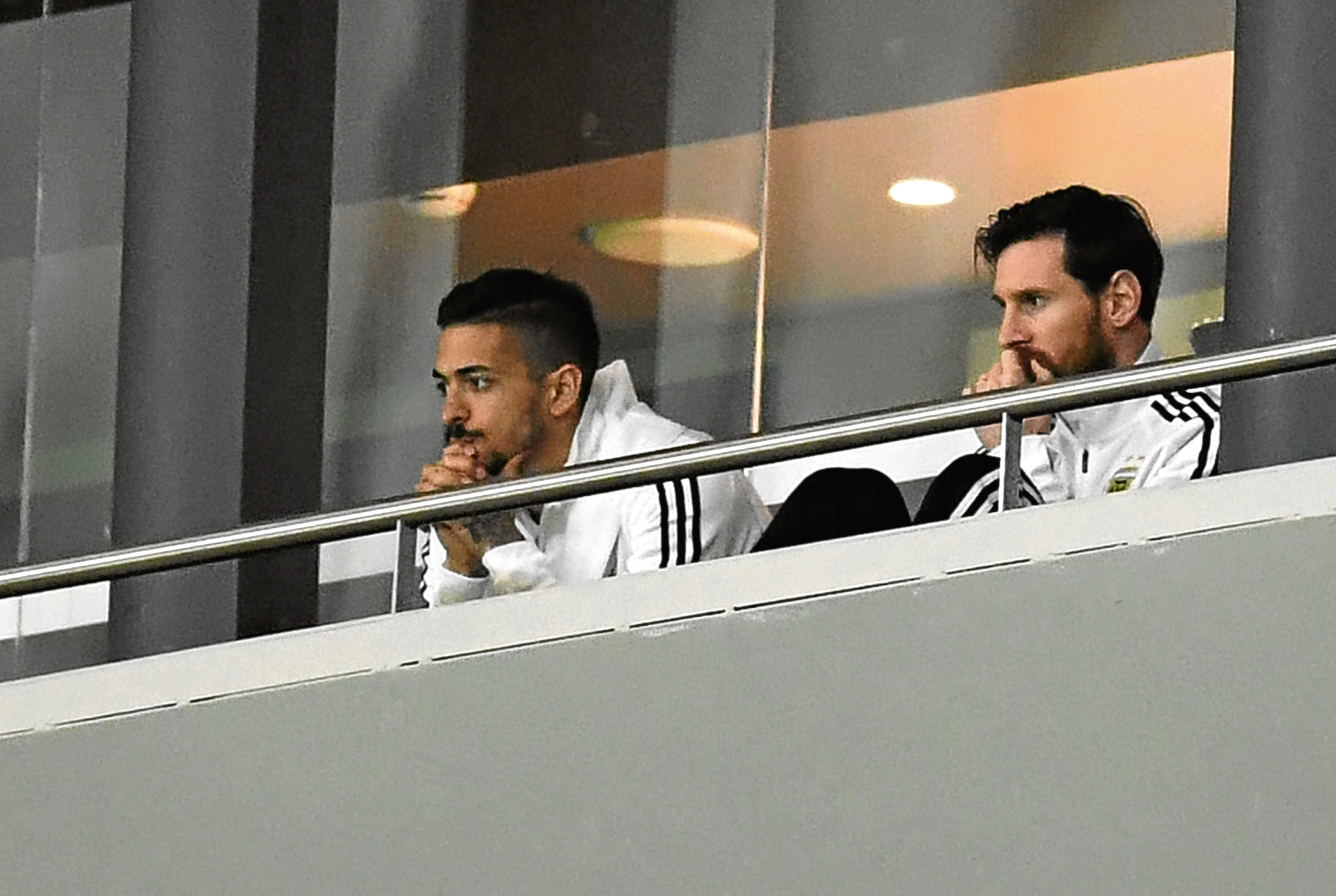 Lionel Messi and Manuel Lanzini watch from the stands during the International Friendly between Spain and Argentina.