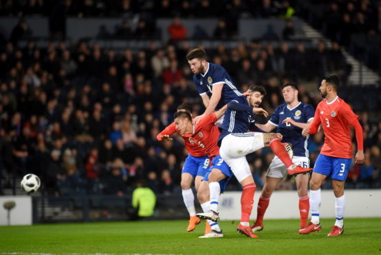 Scotland's Grant Hanley heading at goal.