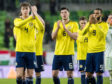 (L-R) Scotland's Jack Hendry, Scott McKenna and Matt Phillips applaud the fans at full-time in Budapest.
