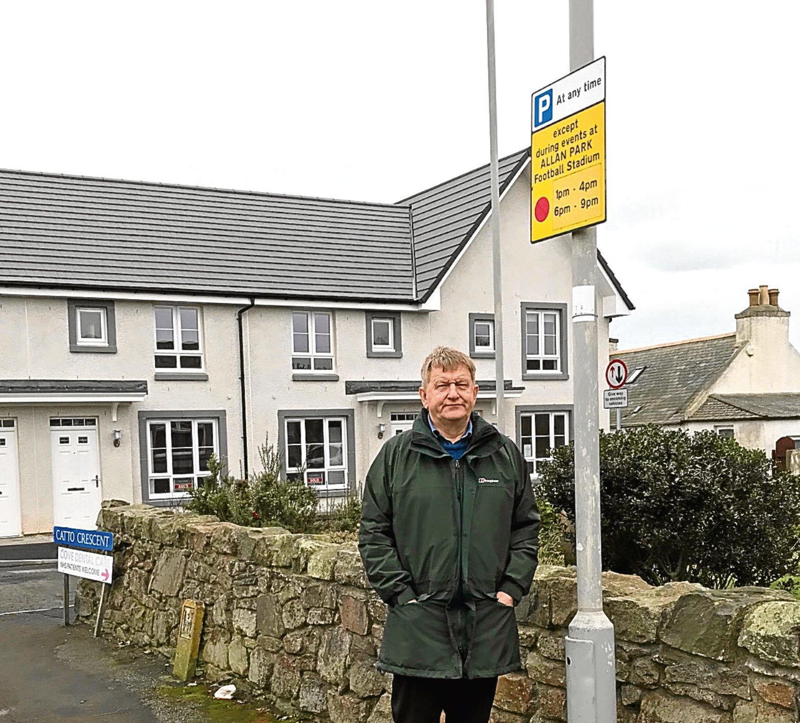 Councillor Alex Nicoll and one of the parking signs outside the houses on the former Allan Park site.