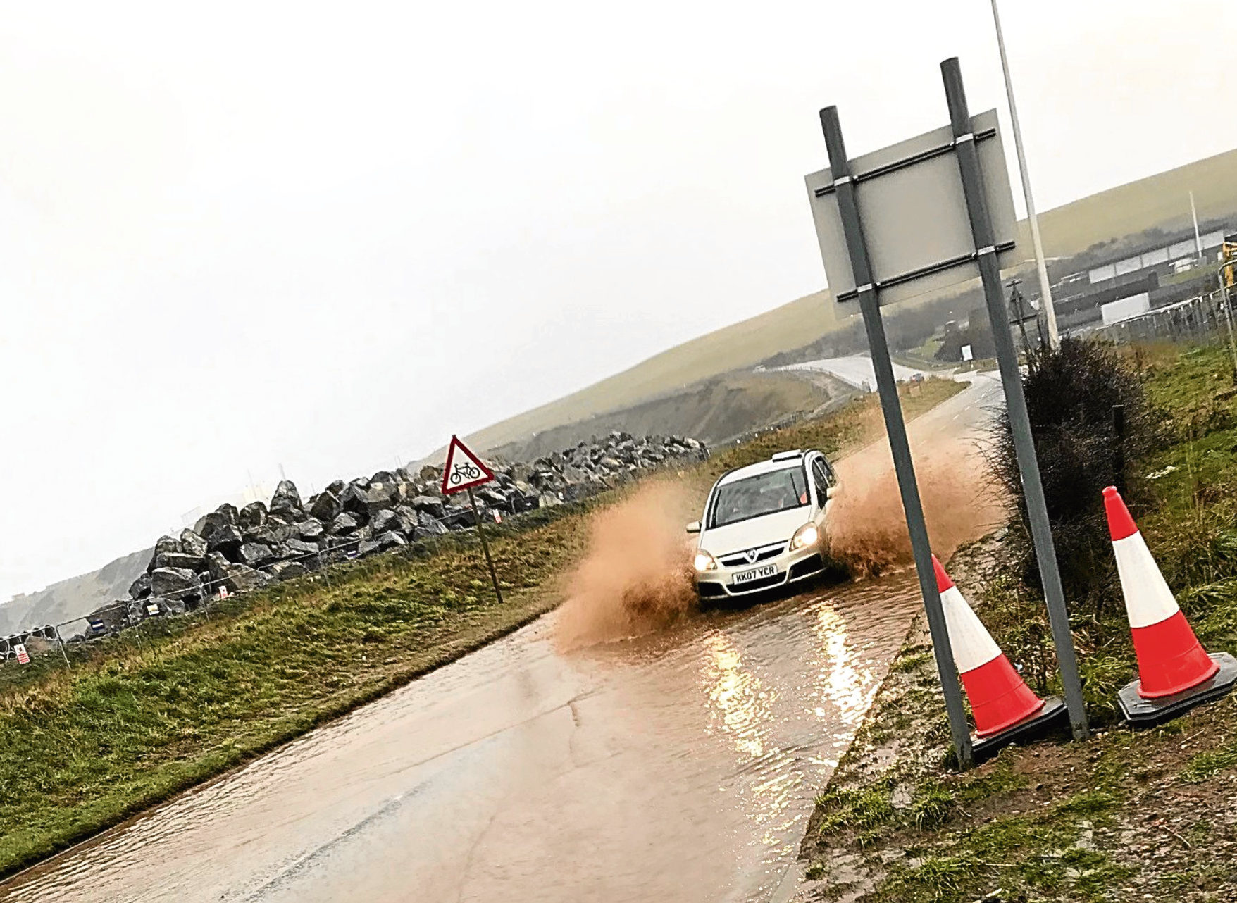 A car negotiating flood water on the Coast Road, Cove.