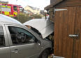 The car crashed through a shed and into the side of the house.