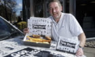 Craig Thomson outside the shop with the Oor Wullie branded fish and chip packaging