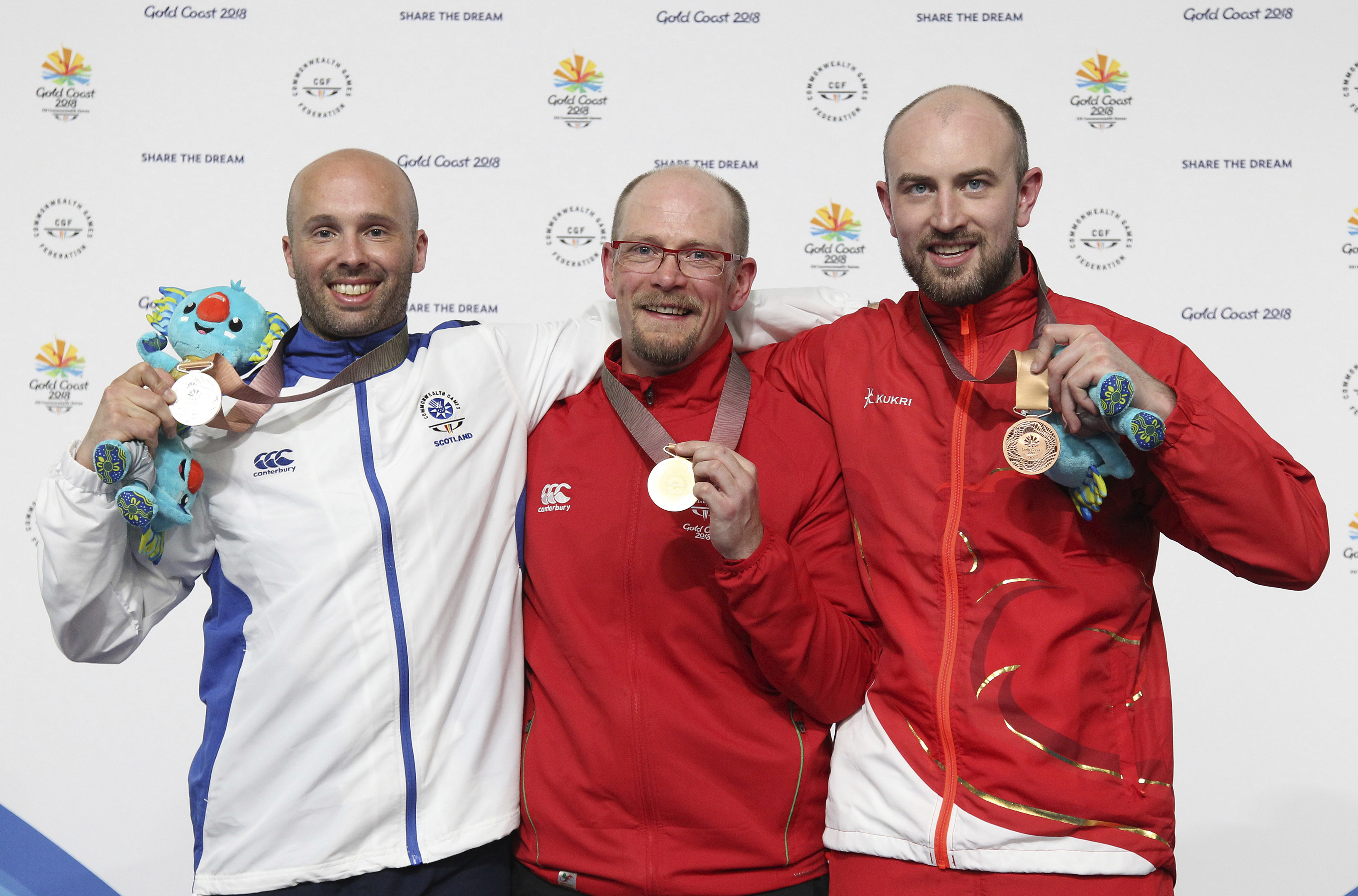 Neil Stirton of Scotland, left, silver medal, David Phelps of Wales, gold medal, center, and Kenneth Parr of England, bronze medal, right, pose during the award ceremony for the men's 50m rifle prone final at the Belmont Shooting Centre during the 2018 Commonwealth Games in Brisbane, Australia.