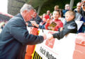 Manchester Utd manager Sir Alex Ferguson signs autographs ahead of a preseason friendly against the Dons