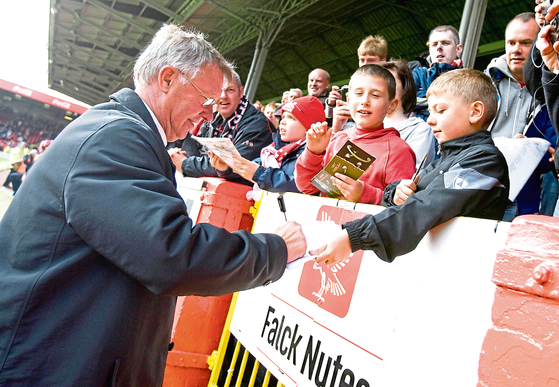 Manchester Utd manager Sir Alex Ferguson signs autographs ahead of a preseason friendly against the Dons
