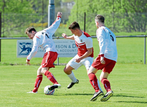 Junior Football. Crombie Park. Culter (red tops) v Colony Park (white tops). Culter's Max Alexander with, left to right, Colony's Andrew Bisset and Darran McGuiness. 12/05/18. Picture by KATH FLANNERY