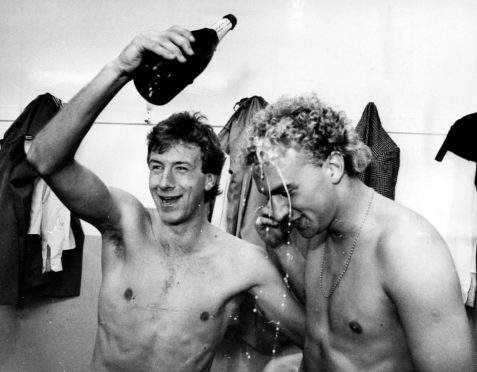 Neil Simpson pours champagne over Neale Cooper's head during title celebrations in 1985.