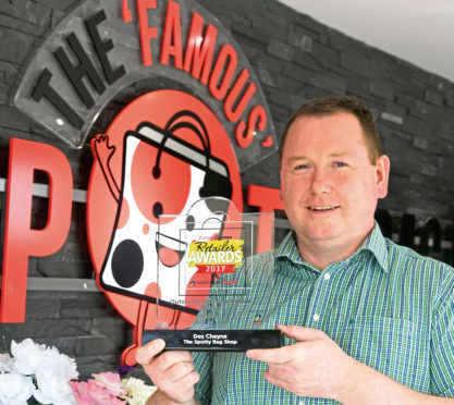 Des Cheye, owner of The Spotty Bag Shop in Banff with his award