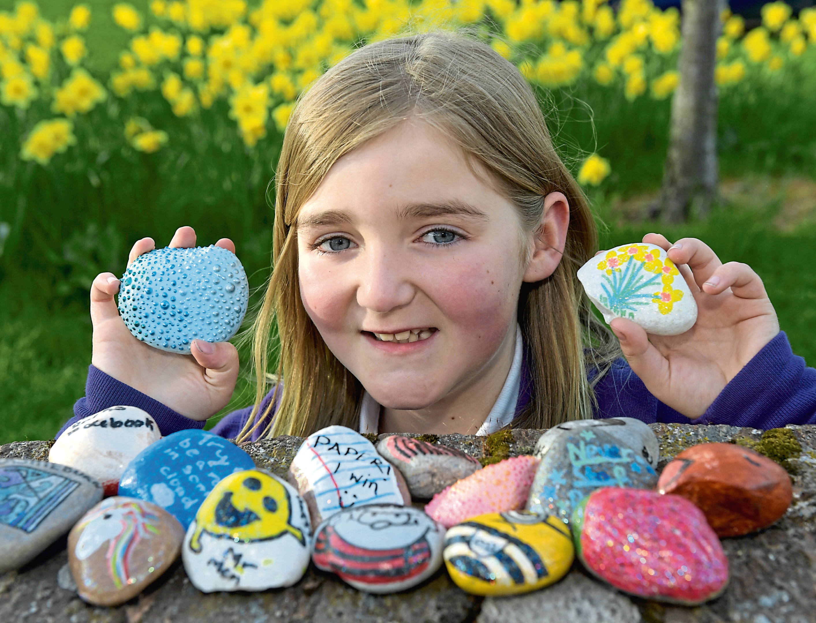 Alana Christie with some of the painted rocks.