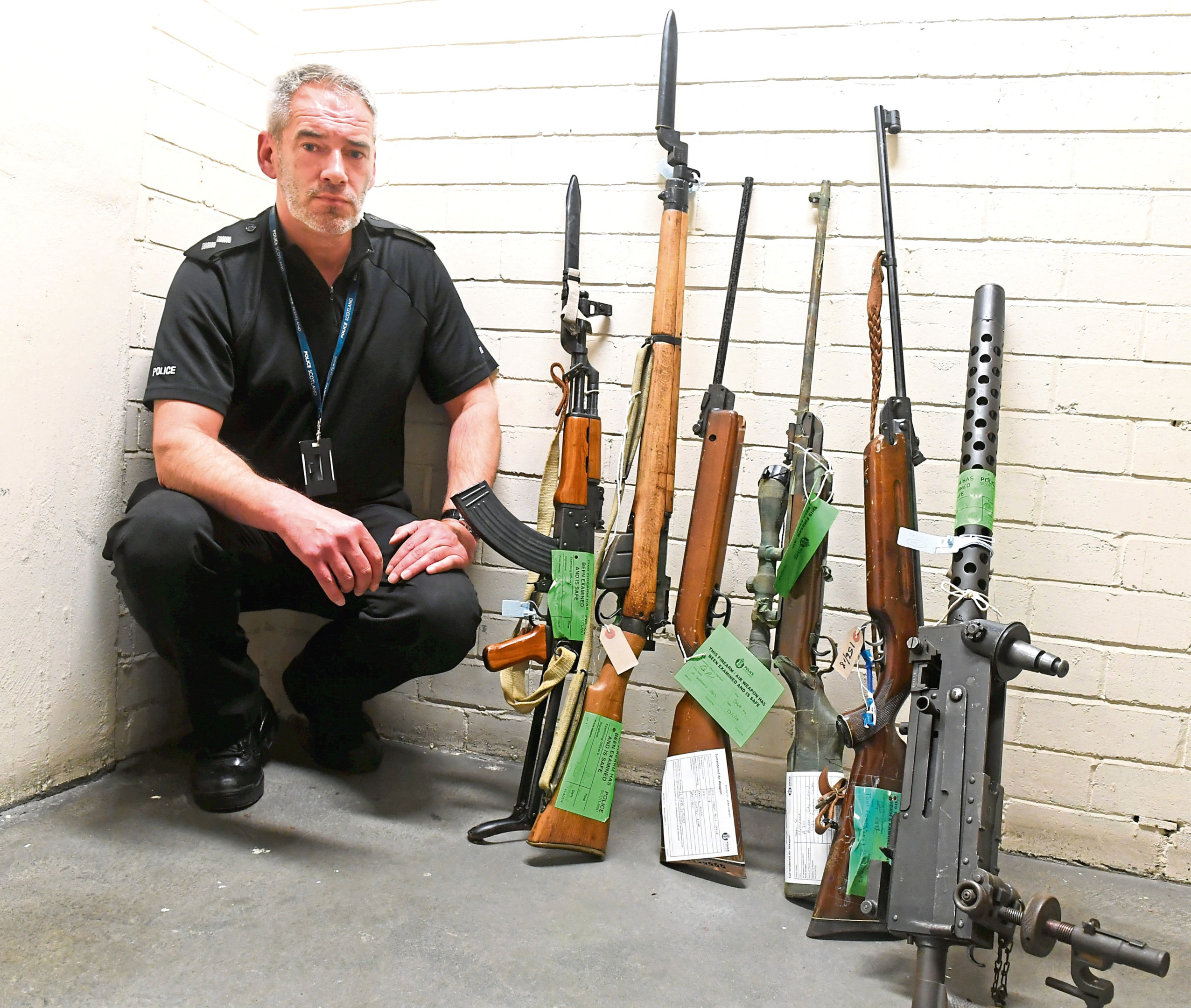 Inspector Mark McLaughlin with some of the firearms that been handed to the police as part of a weapon amnesty