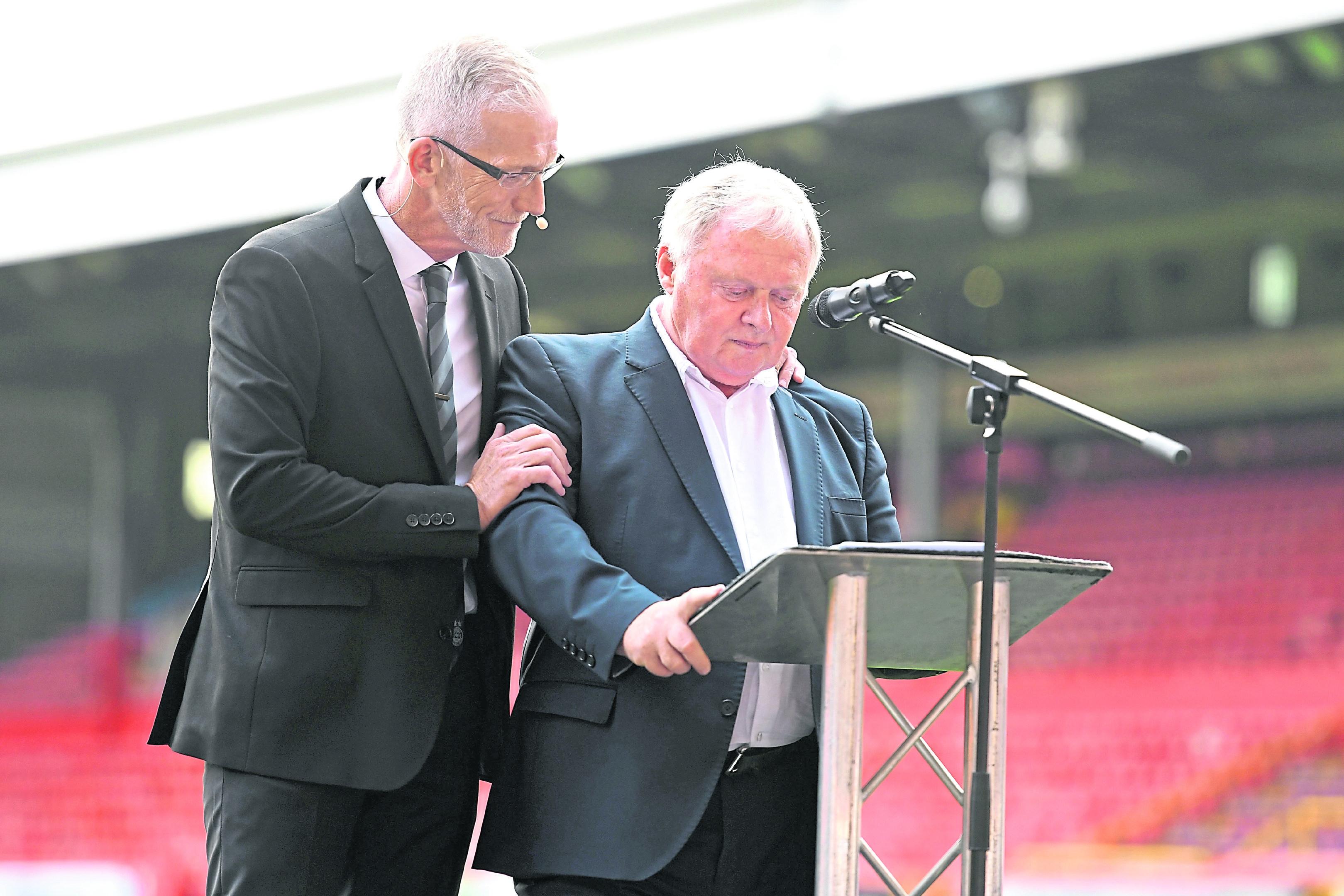 Joe Harper is comforted by host Richard Gordon as he addresses the crowd.