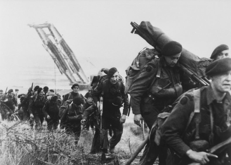 """Royal Marine commandos moving off the Normandy Beaches during the advance inland from """"Sword"""" beach."""