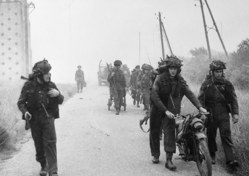 Royal Marines from 48 Commando prepare to push out of the beachhead after landing close to the resort of St Aubin sur Mer.