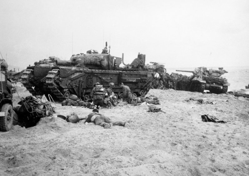 Troops and tanks on a landing beach in Normandy.