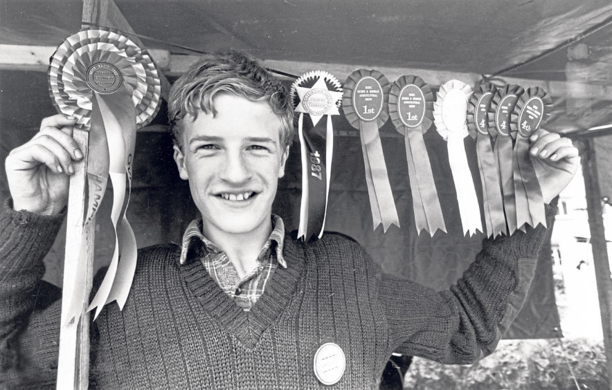 Show president Pat Kemp's 16-year-old son Peter with a string of rosettes the family won at the event