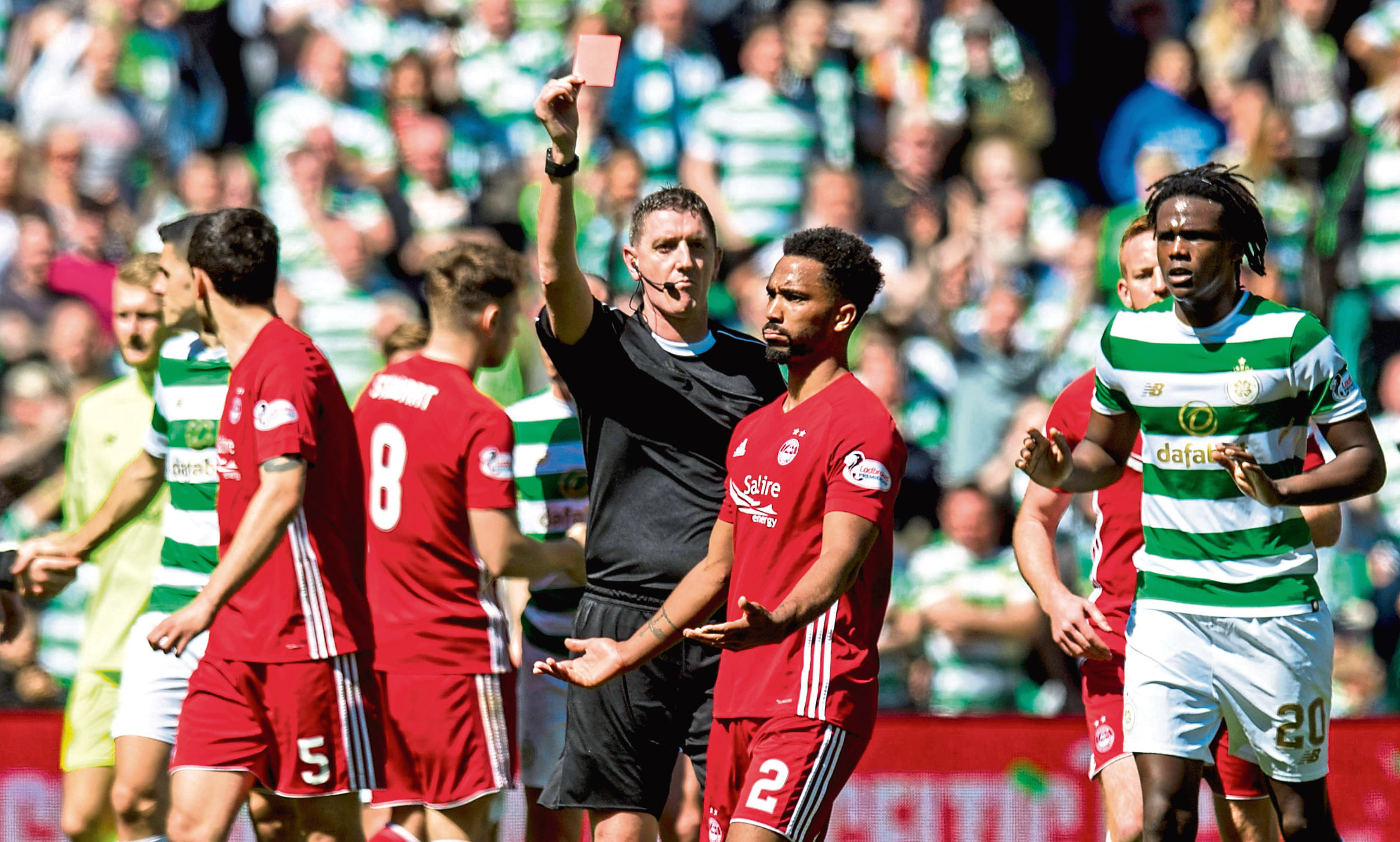 Aberdeen's Shay Logan exchanges words with the Celtic players as he is shown a red card by referee Craig Thomson