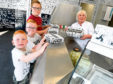 Oor Wullie's manager Sylvia Milne serving the first customers, from left, brothers, Lawrence, Zak and Levi Jaffrey