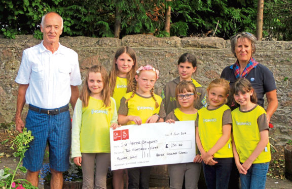 Aboyne Highland Games chairman Alistair Grant presented a cheque to 2nd Aboyne Brownies